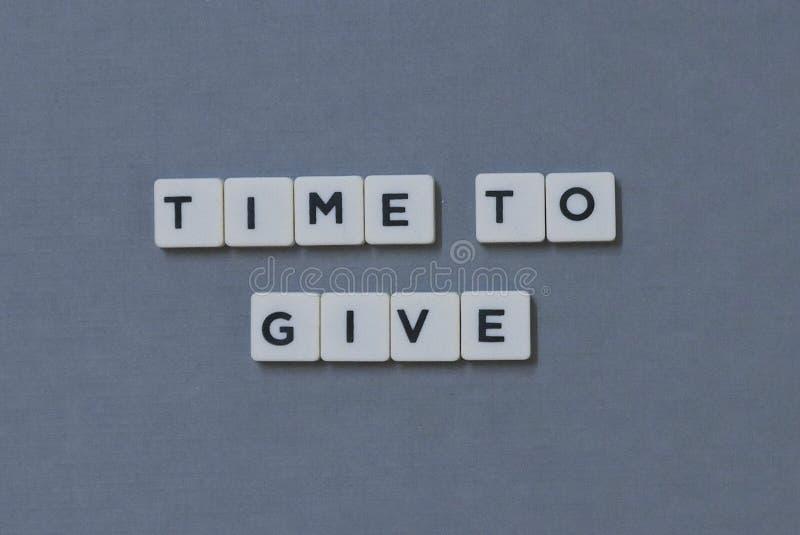 ' Hora de dar ' palavra feita da palavra quadrada da letra no fundo cinzento imagem de stock royalty free