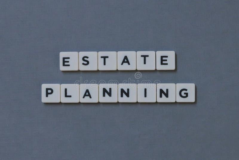 ' Landgoed die ' plannen; woord van vierkant brievenwoord wordt gemaakt op grijze achtergrond die royalty-vrije stock afbeelding