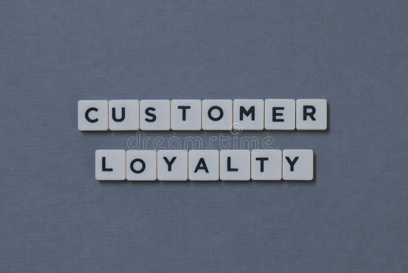 ' Lealtad ' del cliente; palabra hecha de palabra cuadrada de la letra en fondo gris fotos de archivo