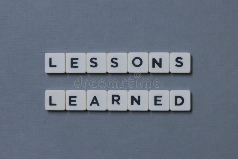 &-x27; Lekcje Uczony &-x27; słowo robić kwadrata listu słowo na popielatym tle zdjęcie stock