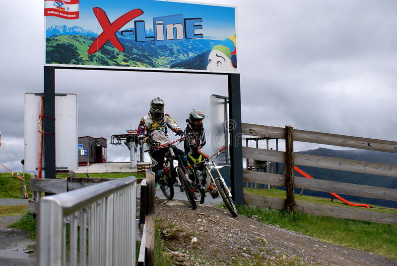 X-Line on Mountain Schatberg, Saalbach,Austria. MOUNTAIN SCHATTBERG ,SAALBACH,AUSTRIA - JULY 10, 2014. Bikers at the starting line at the one of the longest free royalty free stock image
