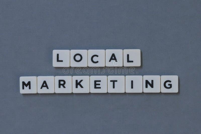 ' Lokale Marketing ' woord van vierkant brievenwoord wordt gemaakt op grijze achtergrond die royalty-vrije stock foto's