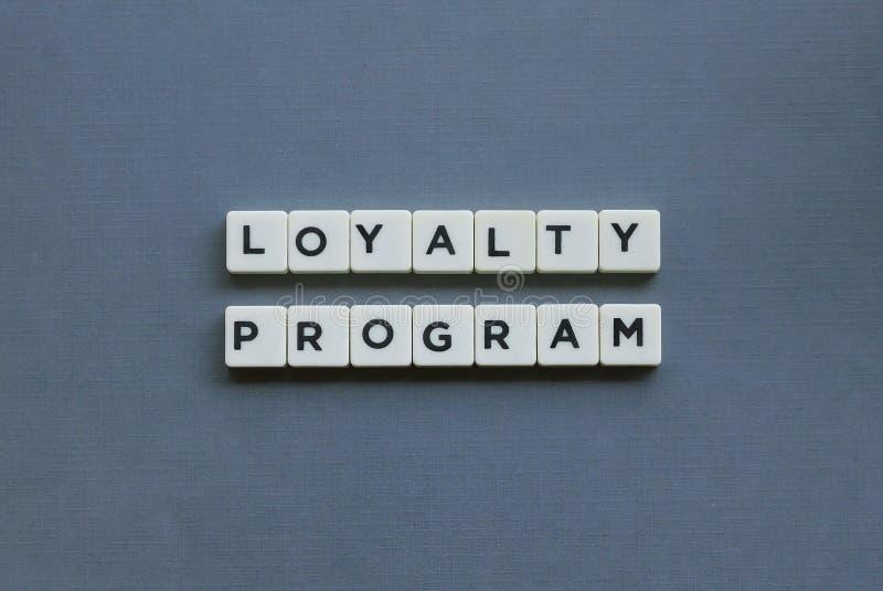 ' Loyaliteitsprogramma ' woord van vierkant brievenwoord wordt gemaakt op grijze achtergrond die royalty-vrije stock afbeelding
