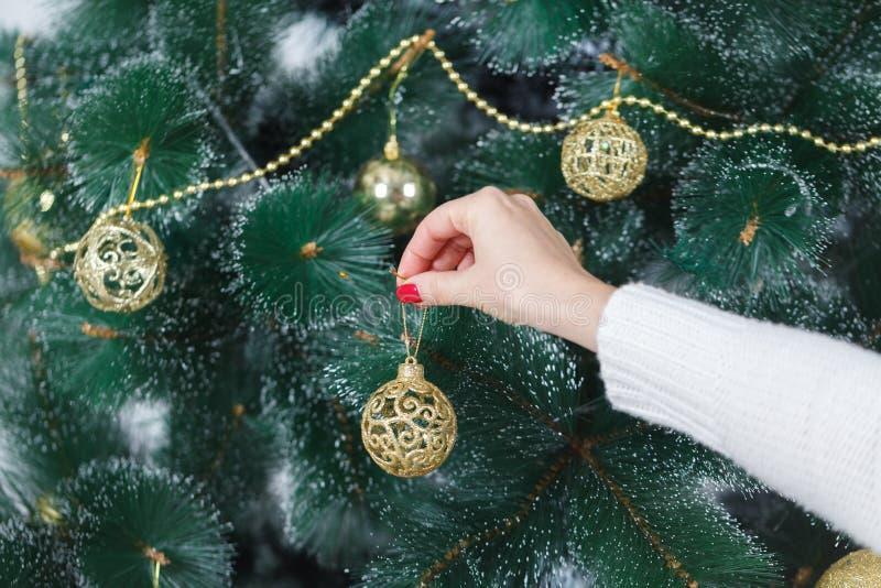 X-mas、寒假和人概念-在家装饰与球的愉快的少妇圣诞树 免版税库存照片