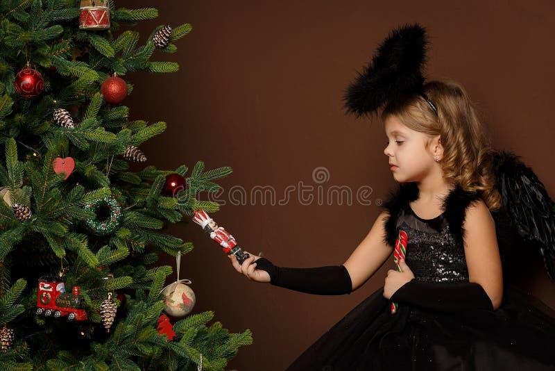 X-mas, каникулы зимы и концепция людей - маленькая девочка в черном костюме ангела сидит на хоботе около рождественской елки и см стоковая фотография