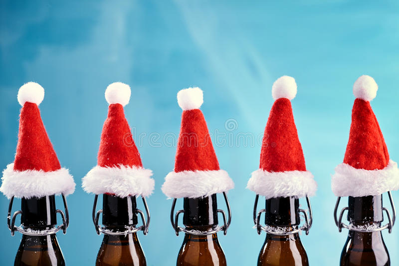 X-mas beer bottles in a row. On blue background with red christmas hats royalty free stock images