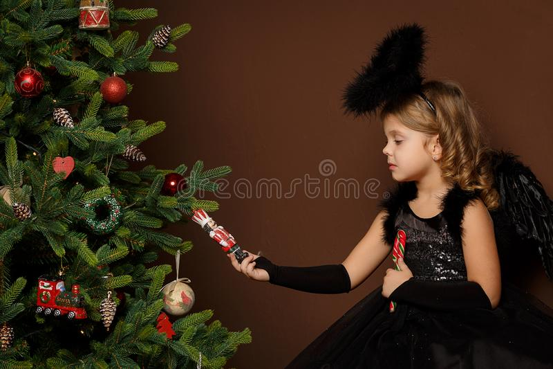 X-mas, férias do inverno e conceito dos povos - a menina no traje preto do anjo senta-se em um tronco perto de uma árvore de Nata fotografia de stock