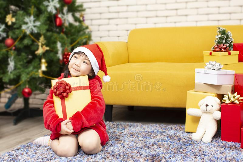 X-mas and holiday concept. Happy childen girl with gift box. Girl in christmas cap hands present wrapped with gold paper and red stock photos