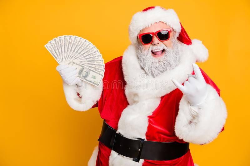 X-mas lottery win credit bank present for noel. Funky crazy hipster white bearded santa claus hold money fan show horned royalty free stock photography