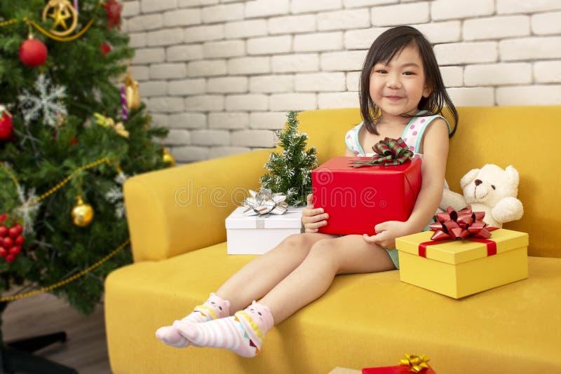 X-mas och feriebegrepp Lycklig barnflicka med gåvaasken Flicka i röd gåva för jullockhänder som slås in med guld- papper och royaltyfri bild