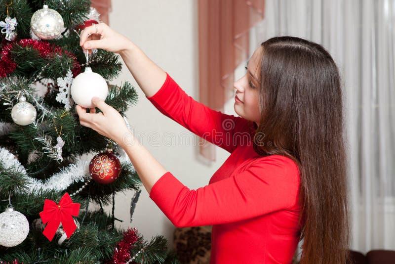 X-mas, vinterferier och folkbegrepp - lycklig ung kvinna som dekorerar julträdet med den hemmastadda bollen royaltyfria foton