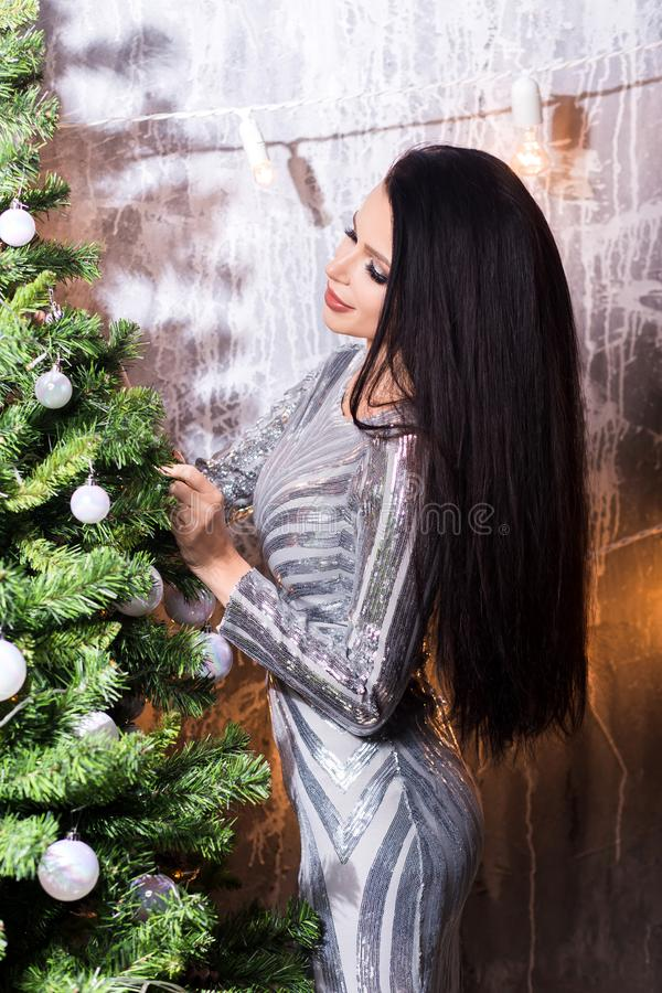 X-mas, winter holidays and people concept - happy young woman decorating christmas tree with ball at home. Beautiful brunette woman decorating a christmas tree stock photography