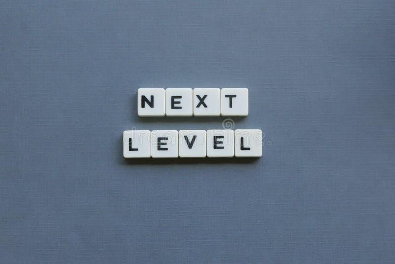 ' Nivel siguiente ' palabra hecha de palabra cuadrada de la letra en fondo gris foto de archivo libre de regalías