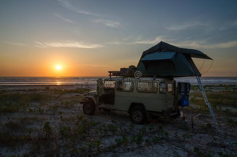 4x4 offroad vehicle with roof top tent camping on beach during sunset, Casamance, Senegal, Africa stock photography