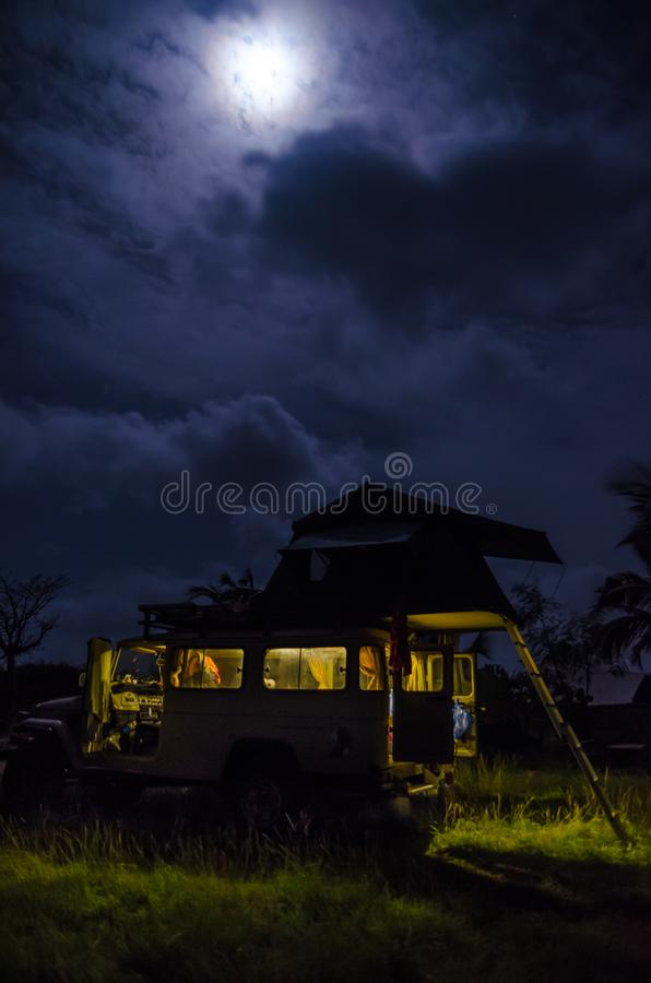 4x4 offroad vehicle with roof top tent and interior light during night with cloudy sky and strong moon, camping concept.  stock photography