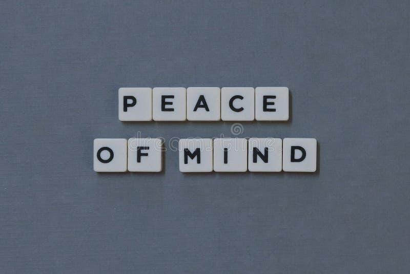 & x27; Paz de espírito & x27; palavra feita da palavra quadrada da letra no fundo cinzento imagens de stock royalty free