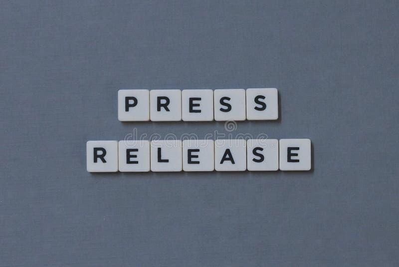 ' Persmededeling ' woord van vierkant brievenwoord wordt gemaakt op grijze achtergrond die stock foto's
