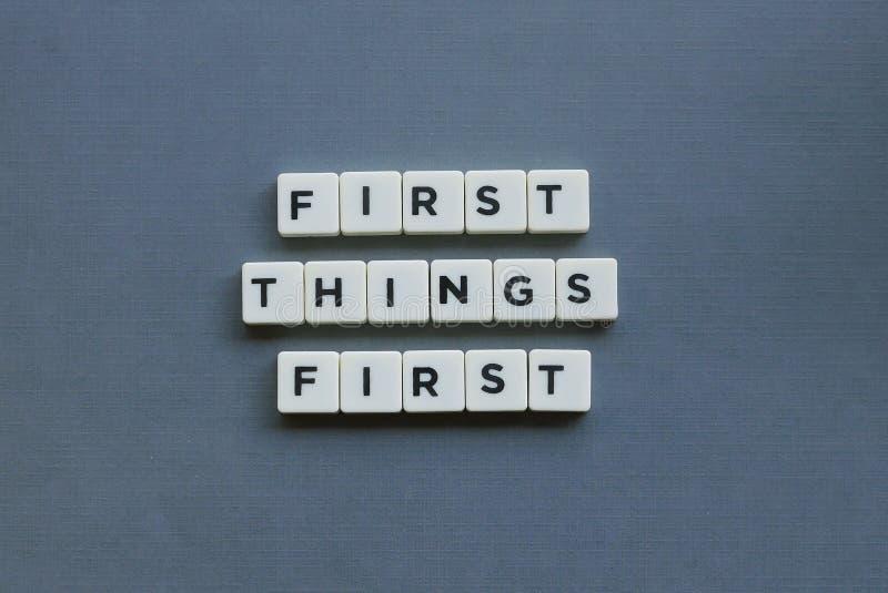 &#x27 ; Premières choses premier &#x27 ; mot fait en mot carré de lettre sur le fond gris photographie stock libre de droits