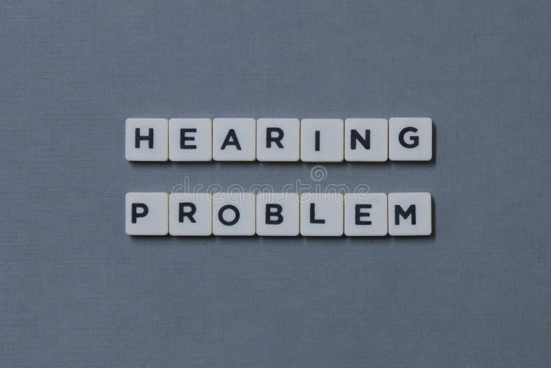 ' Problema ' de la audición; palabra hecha de palabra cuadrada de la letra en fondo gris fotos de archivo libres de regalías