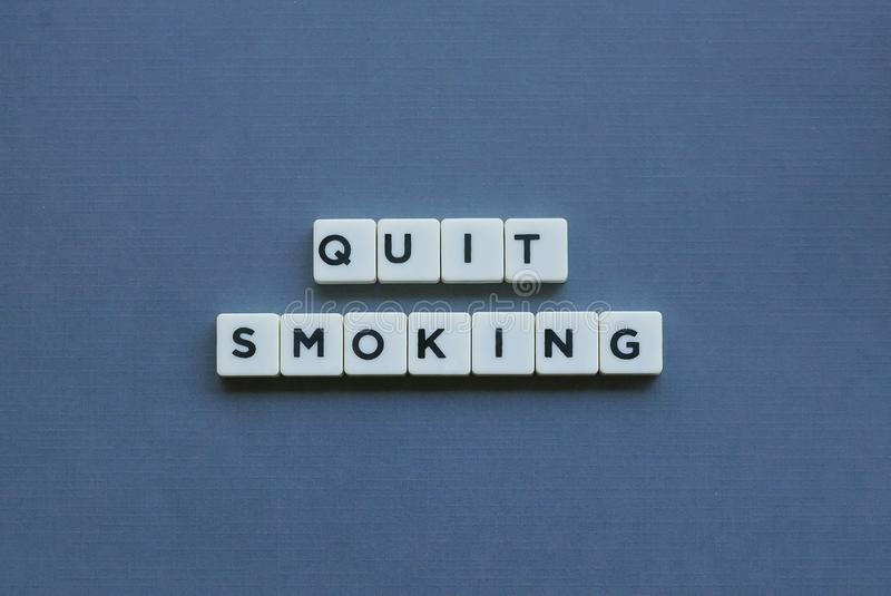 & x27; Quit Smoking & x27; word made of square letter word on grey background royalty free stock image