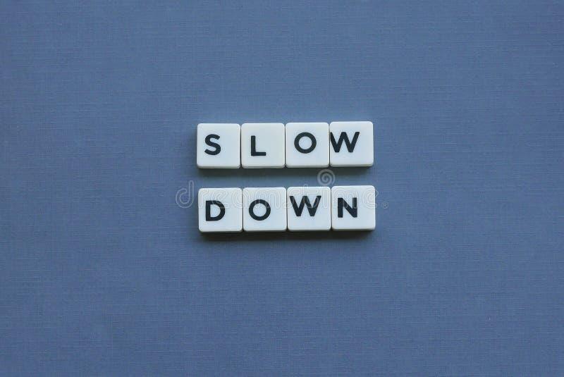 ' ; Ralentissement ' ; mot fait en mot carré de lettre sur le fond gris photos stock
