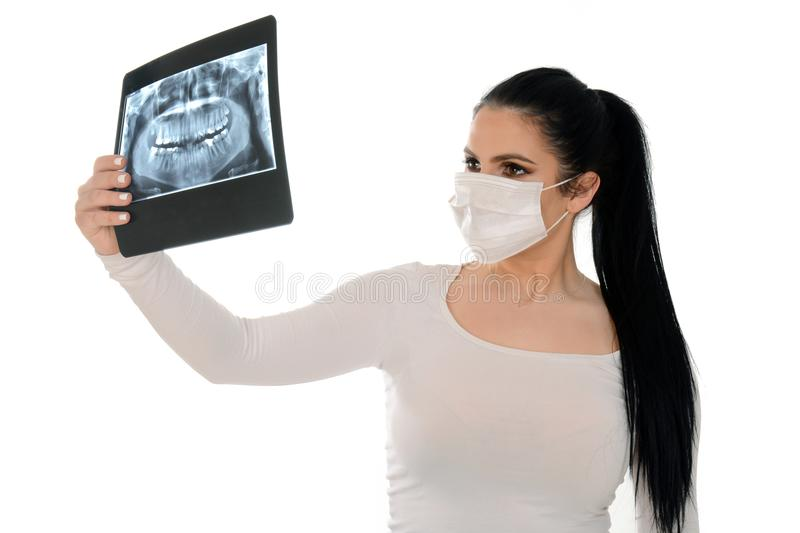 X-ray of a human jaw in the hands of the dentist. Beautiful girl holding x-ray, wearing protective mask stock photography