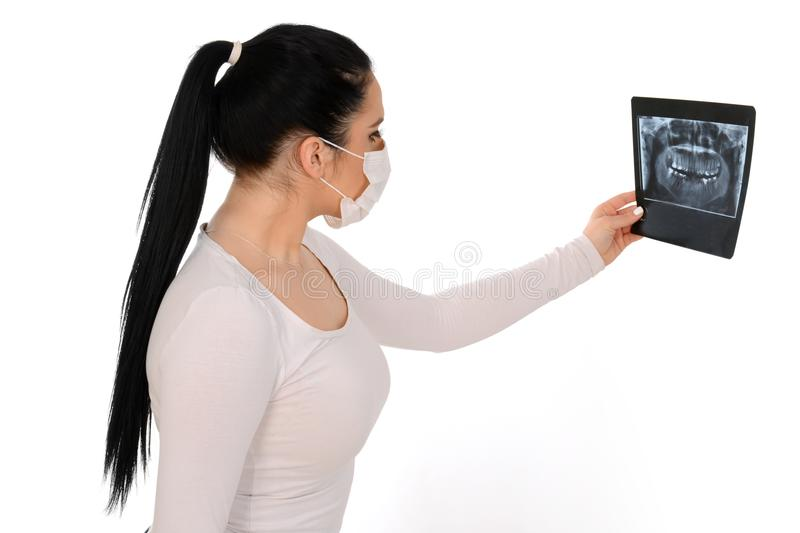X-ray of a human jaw in the hands of the dentist. Beautiful girl holding x-ray, wearing protective mask stock photos