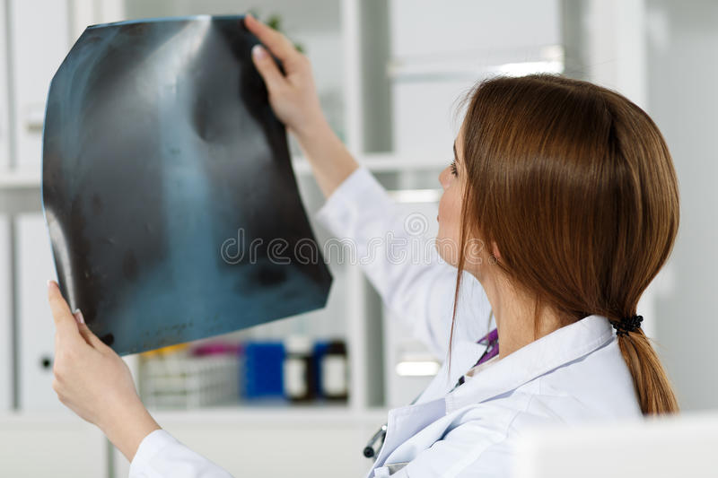 X-ray picture. Young beautiful female medical doctor examining x-ray photography of patient to detect problem. Medical concept. Traumatologist holding x-ray stock photography