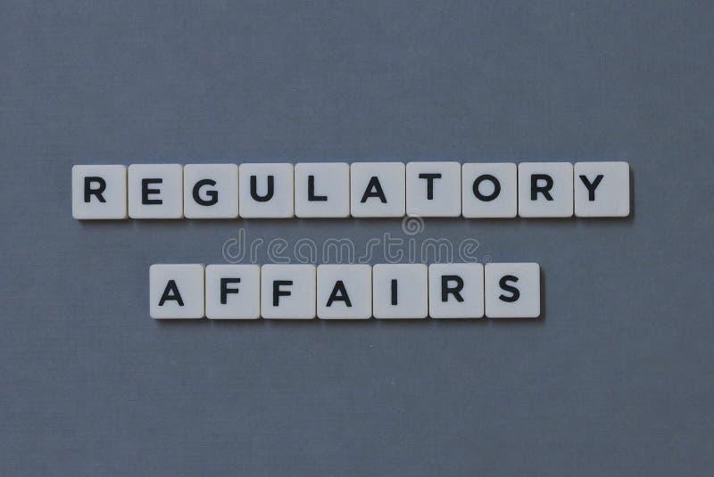 ' Reglerande angelägenheter ' ord som göras av fyrkantigt bokstavsord på grå bakgrund arkivbilder