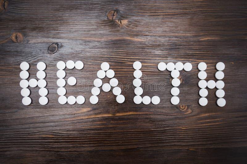 X22 & słowo; health& x22; kłaść out z wielkimi białymi pigułkami na ciemnym drewnianym tle obraz royalty free