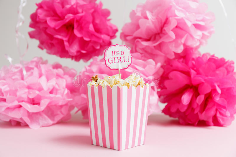 It& x27;s a girl sign in a popcorn bag at the baby shower party. Pap. Er flowers background. Baby shower celebration concept. Festive party background stock photo