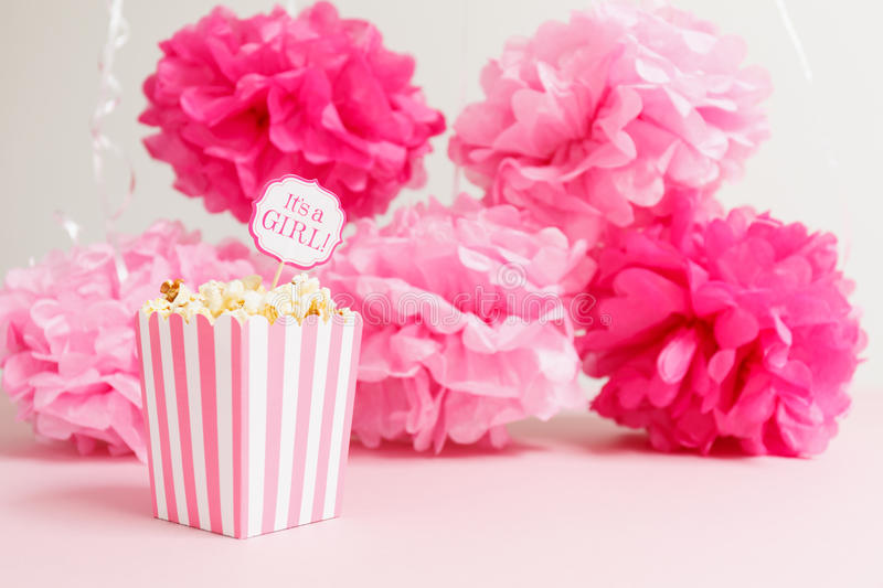 It& x27;s a girl sign in a popcorn bag at the baby shower party. Pap. Er flowers background. Baby shower celebration concept. Festive party background stock images
