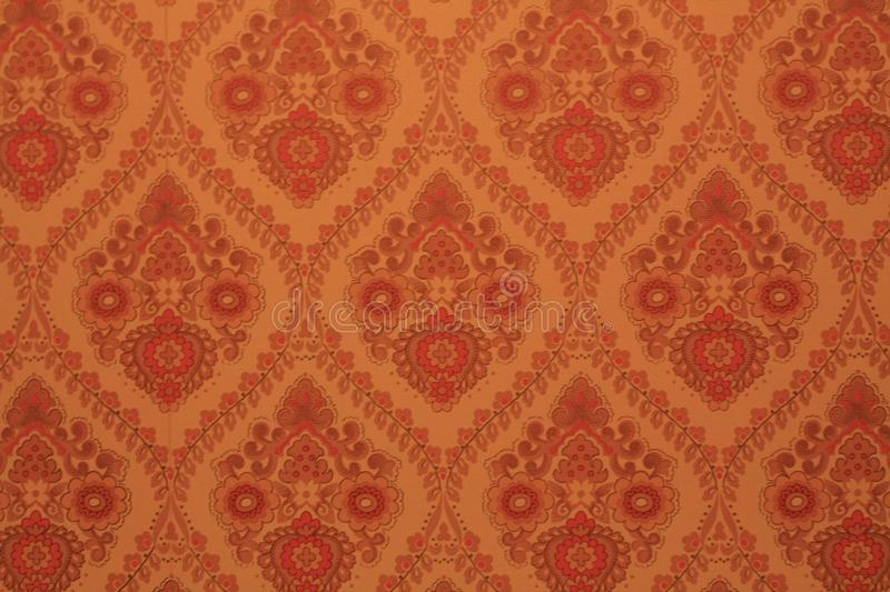 70's wallpaper with repeating paisley pattern. Orange 70's wallpaper with repeating paisley pattern in an old house royalty free stock photo