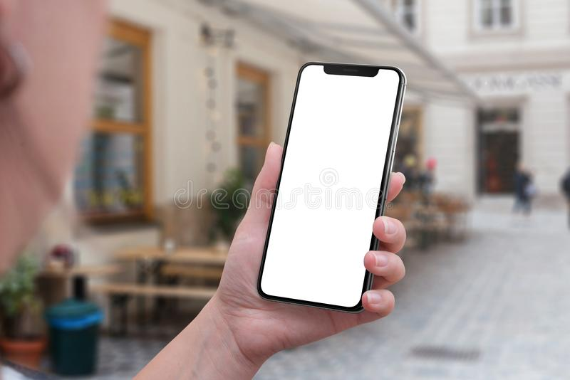 X smartphone in woman hand. Isolated screen for user interface mockup. City street in background royalty free stock photography