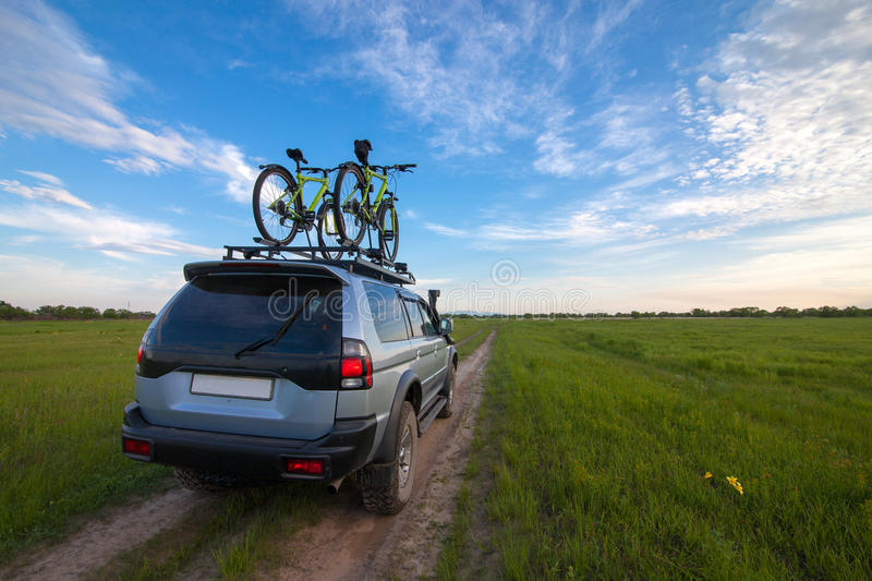 4x4 SUV with two bicycles on roof rack stock photography