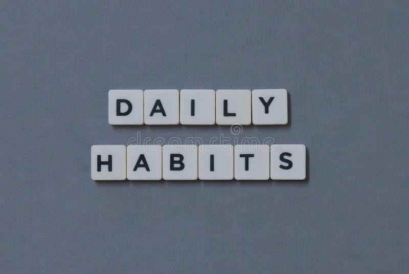 ' Tägliche Gewohnheiten ' Wort gemacht vom quadratischen Buchstabewort auf grauem Hintergrund lizenzfreie stockfotografie
