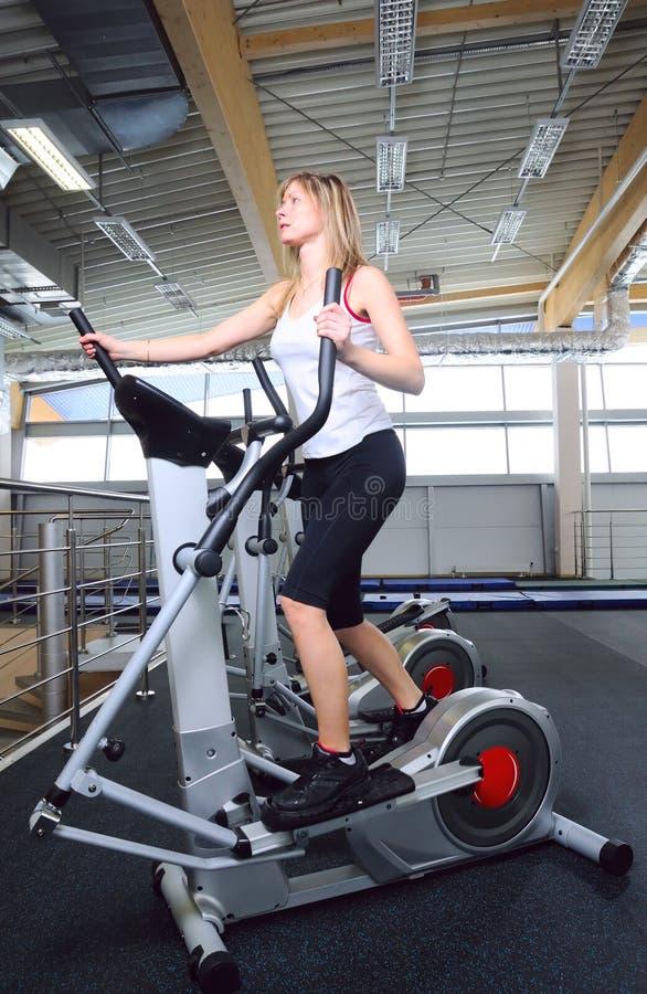 X-trainer. Slim woman on cardio machine stock photography
