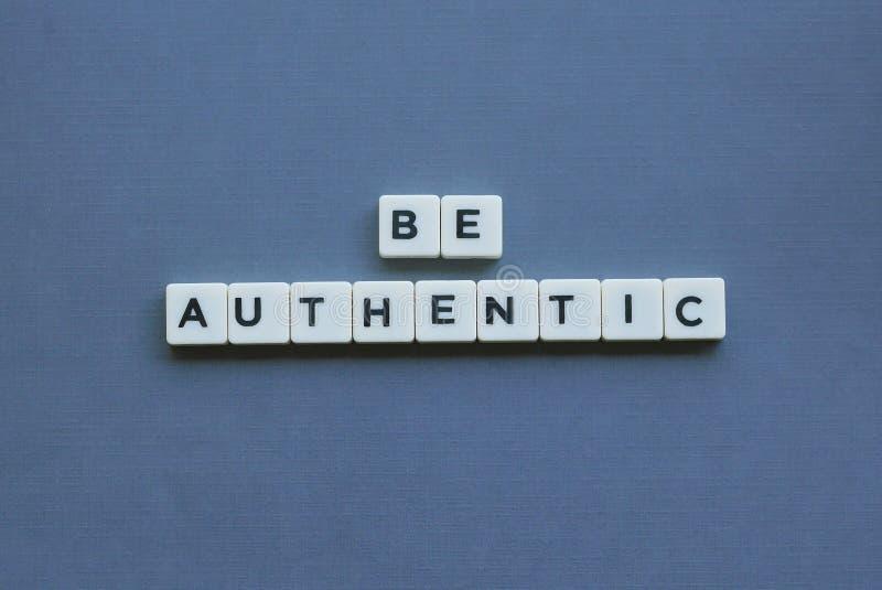 ' Var autentisk ' ord som göras av fyrkantigt bokstavsord på grå bakgrund royaltyfri foto