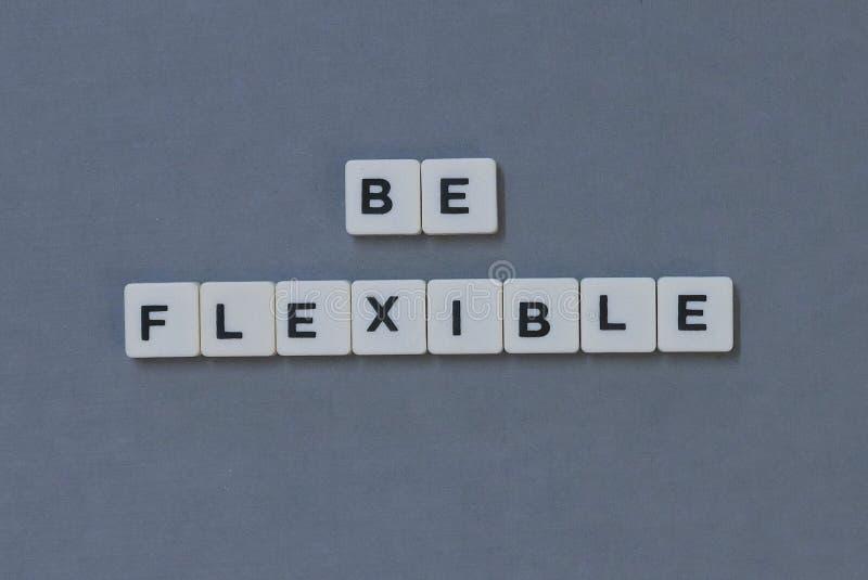 & x27; Var böjlig & x27; ord som göras av fyrkantigt bokstavsord på grå bakgrund fotografering för bildbyråer