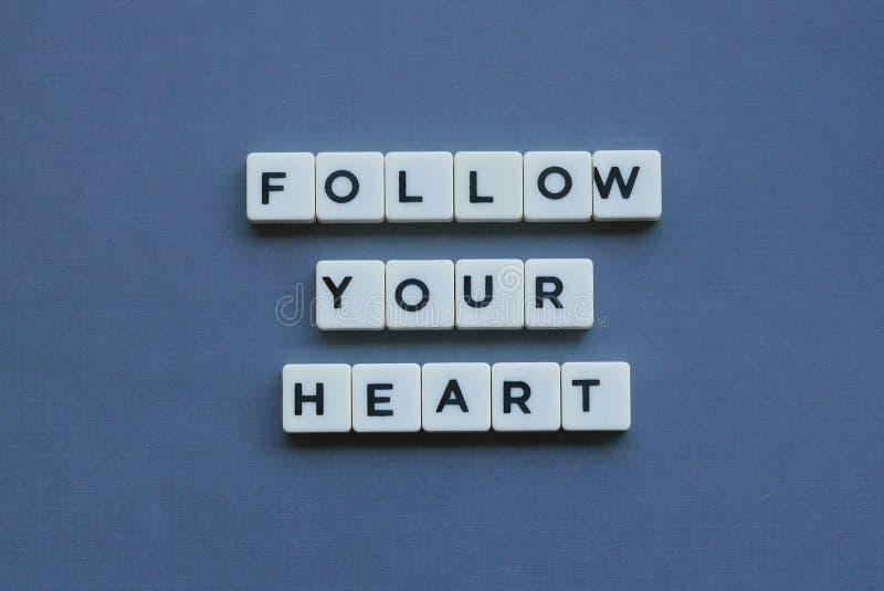 ' Volg Uw Hart ' woord dat van vierkant brievenwoord wordt gemaakt op grijze achtergrond stock afbeelding