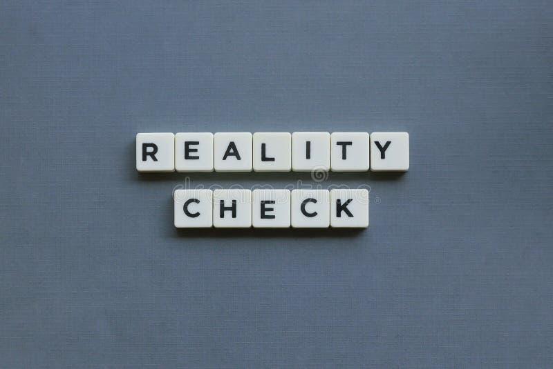 ' Werkelijkheidscontrole ' woord van vierkant brievenwoord wordt gemaakt op grijze achtergrond die royalty-vrije stock foto