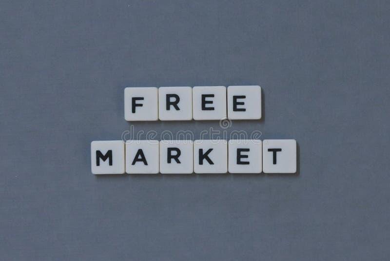 &-x27; Wolny Rynek &-x27; słowo robić kwadrata listu słowo na popielatym tle obrazy stock