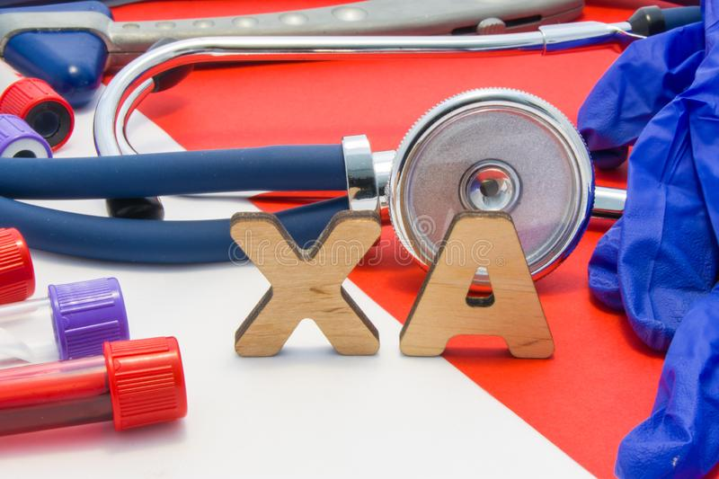 XA medical abbreviation meaning LMW heparin in blood in laboratory diagnostics on red background. Chemical name of XA is surrounde. D by medical laboratory test stock image