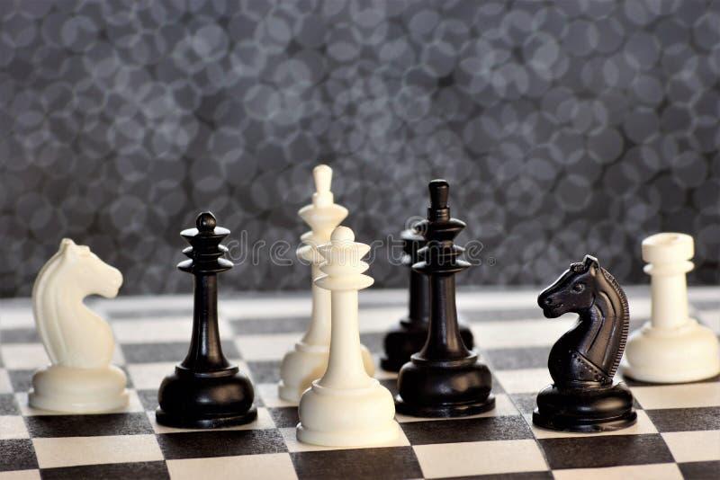 A xadrez é um jogo antagônico da lógica antiga popular da placa com partes preto e branco especiais, em uma placa da pilha para d fotografia de stock
