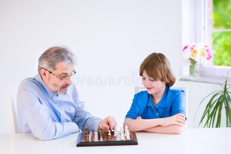 Xadrez de jogo de primeira geração feliz com seu neto fotos de stock royalty free