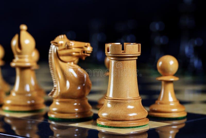 A xadrez remenda a gralha, o cavaleiro, o bispo e o penhor na placa de xadrez fotografia de stock