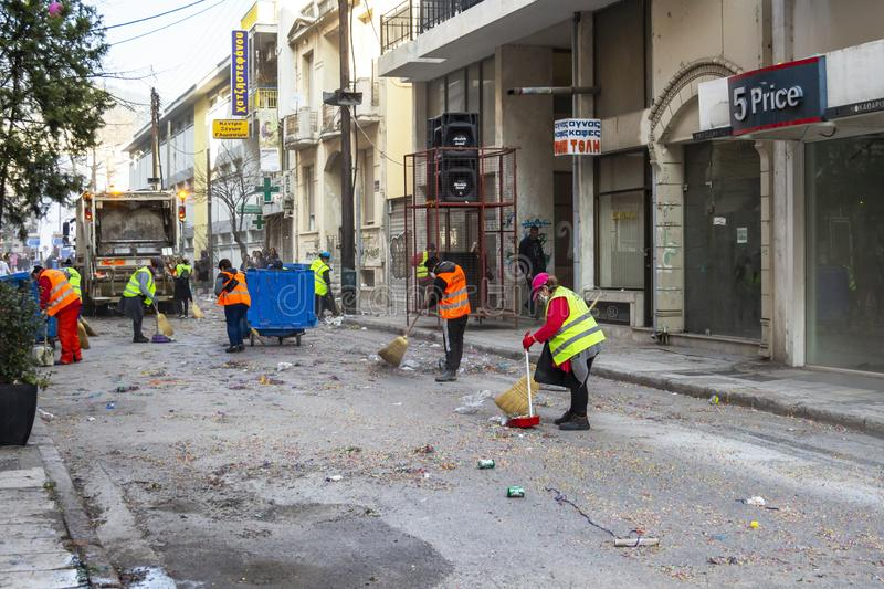 People clean the streets right after the carnival parade in Xanthi, Northeastern Greece. XANTHI, GREECE - MARCH 10, 2019: People clean the streets right after stock photos