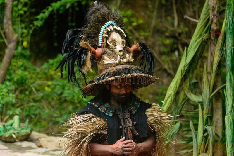 Mayan people in Mexico. XCARET, MEXICO - NOV 8, 2015: Unidentified man wears a costume of a Maya indian. Maya people are a group of Indigenous people of royalty free stock photography