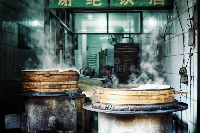 Young chinese woman preparing dumplings at a small street eatery restaurant stock photo