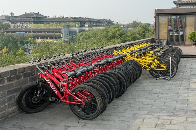 Rental bikes for the city wall in Xian, China. XI`AN, CHINA - 17 OCTOBER 2018: Rental bikes on the city wall in Xian on smoggy day stock photo